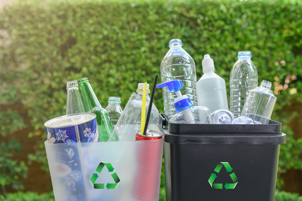 Close up plastic and  glass bottle in the bins for separating recycle materials from the garbages. Reducing waste by following the green concept. Recycling process.